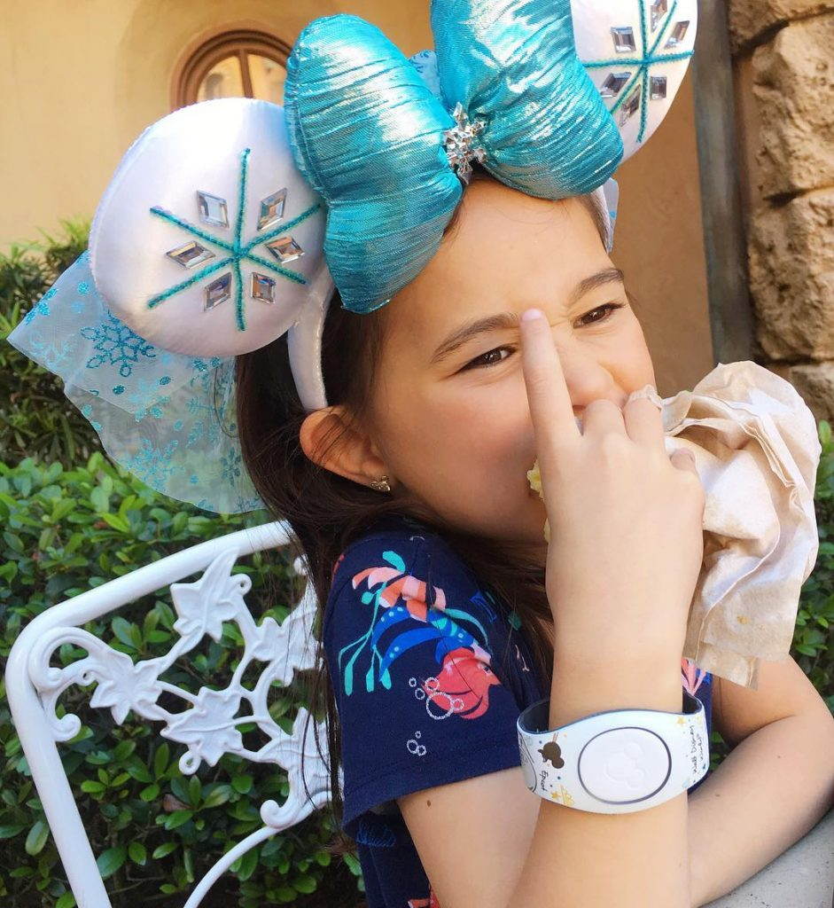 girl wearing Frozen Mickey Ears and MagicBand, eating Nudel Gratin
