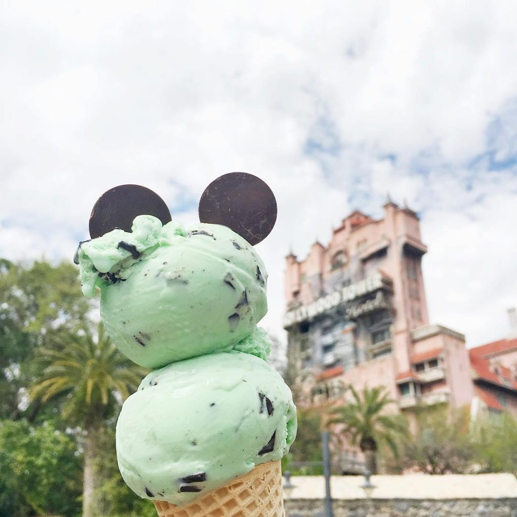 double scoop of mint chocolate chip ice cream with Mickey ears, and the Hollywood Tower Hotel in the background