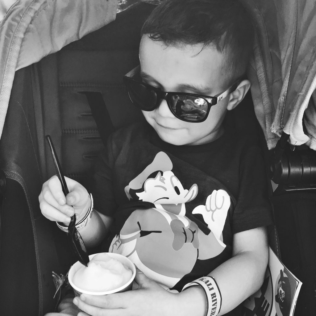 black and white image of little boy wearing sunglasses and Donald Duck t-shirt, eating Dole Whip