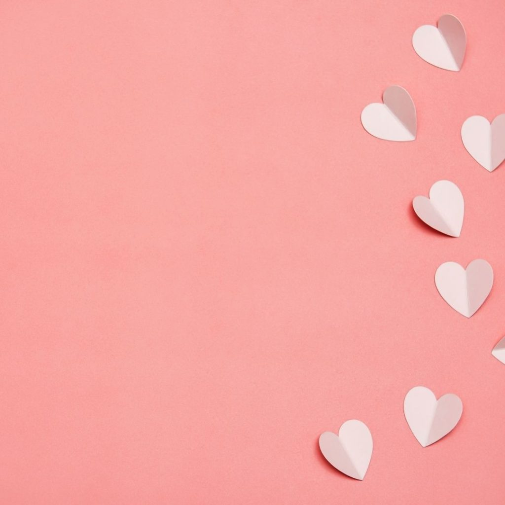 peachy pink background with cut paper hearts